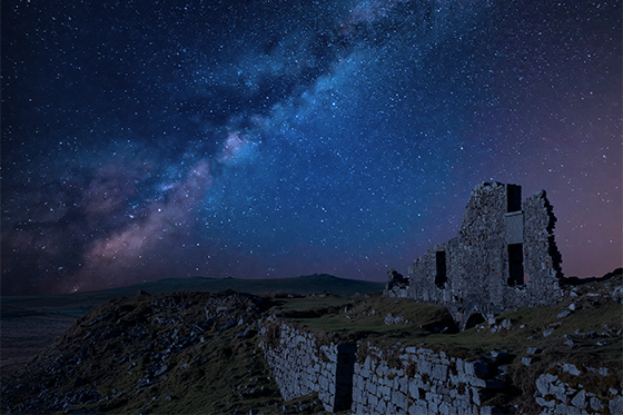 Festive Story Prompt, image of a starry night sky with the crumbling ruins of a castle in the foreground.